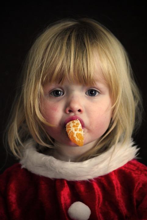 niña comiendo mandarina en navidad